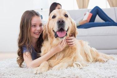 Girl embracing Golden Retriever while lying on rug