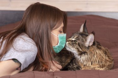 woman with mask holding her face to cat's face