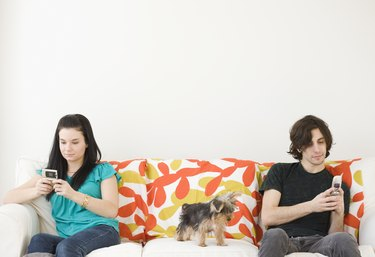 Man and woman dialing cell phones on opposite ends of sofa