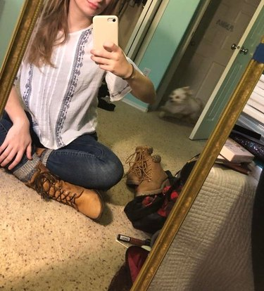 Woman taking selfie in mirror while small white dog runs into the room behind her