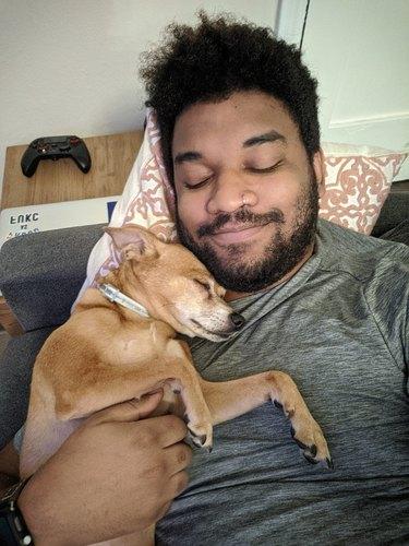 man and dog sleep on couch