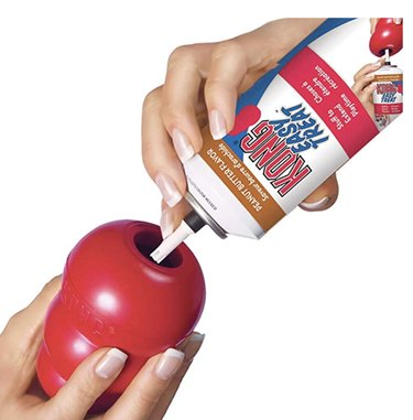 a red rubber Kong being filled with a spray treat