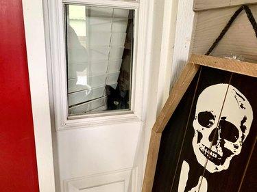 black cat peers out window