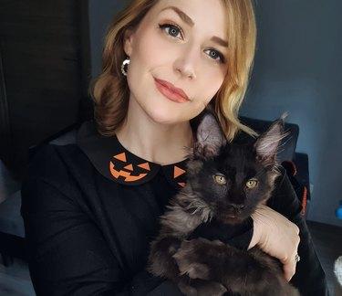 women in halloween sweater holds black cat