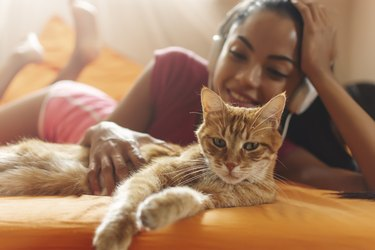 Happy woman at home listening music and cuddle her cat