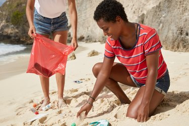 Females clean trash from beach,carrying red litter bag.