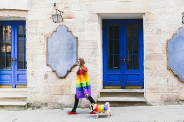 Young woman and her dog enjoying the great city walking in rainbow clothing