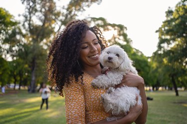 Woman and her white poodle in a dog park