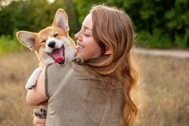Young woman with laughing corgi puppy outside
