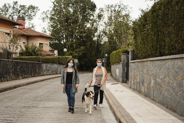 front view of two women walking down the street with her dog wearing a face mask to protect themselves