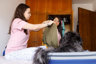 Two young women choosing clothes to pack travel bag
