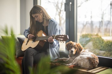 Woman playing guitar in living room while her dog lying next to her