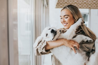 Young woman cuddles her 12 week old Golden Retriever Puppy