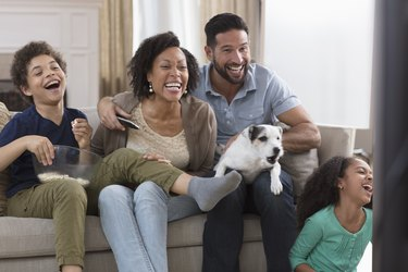 family having fun and watching tv with a barking dog on man's lap