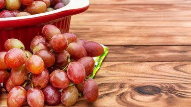 Ceramic pot with red grapes on wooden table. Space for text.