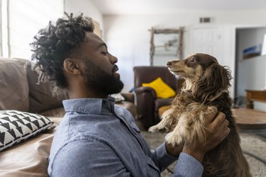 Young black man playing with his dog