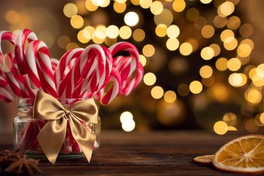 Candy canes on the christmas table tied with a gold bow