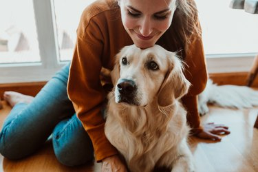 Smiling Woman With Dog Sitting On Floor At Home
