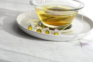 Aromatic medical chamomile tea whit chamomile/daisy flowers served on white wooden table
