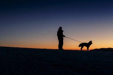 man walking dog against sunset