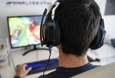 Boy with headphones playing a game on his computer