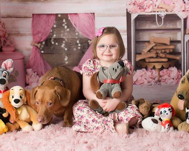 girl and dog pose with dolls