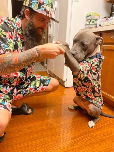 dog and person dressed in matching floral shirts