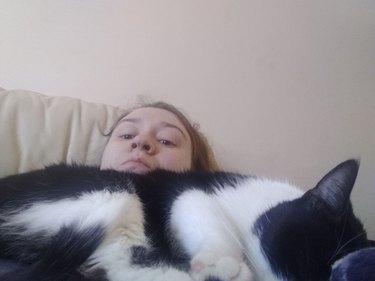 big cat sleeps on woman