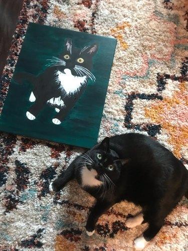 woman paints portrait of cat