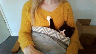 woman craddles cat in blanket