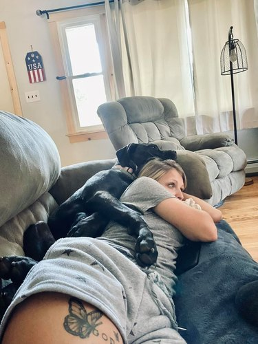 dog spoons woman on couch
