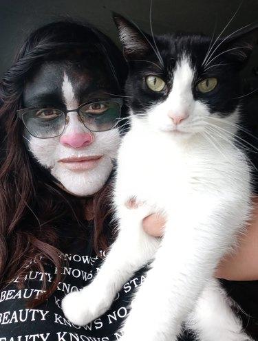 woman gets facepaint to match cat's coat