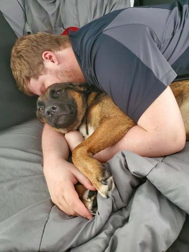 man snuggles with girlfriend's dog