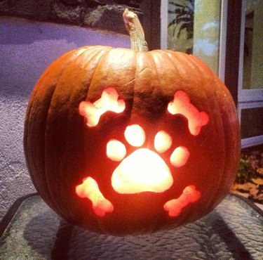 dog's paw print carved into pumpkin