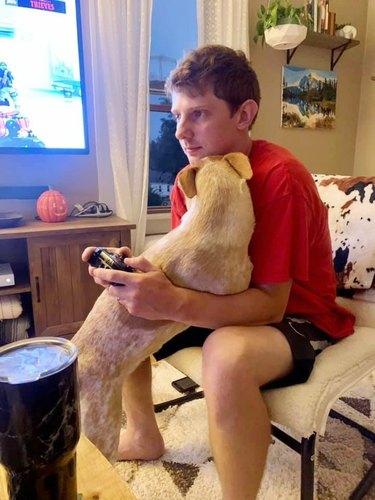 dog hugs man playing video games