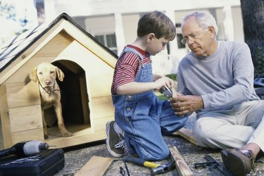 Grandfather and his grandson building a kennel