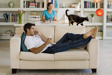 Couple with cat relaxing at home
