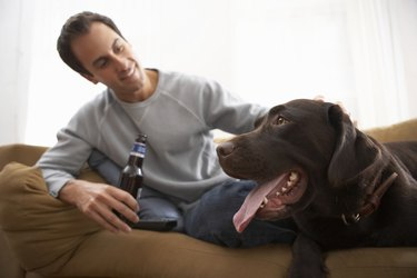 Man holding bottle relaxing on sofa with dog, smiling