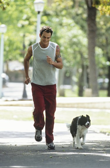 Mid adult man jogging with dog in park