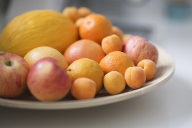 Plate of fresh fruit in kitchen, close up