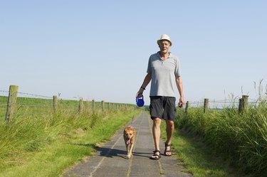Elderly man walking the dog