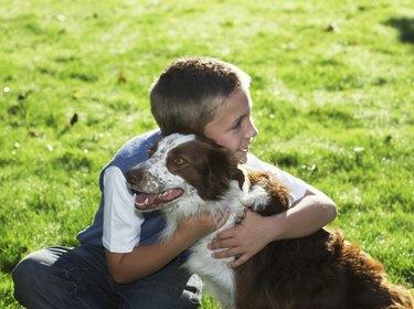 Boy (7-9) hugging dog, smiling