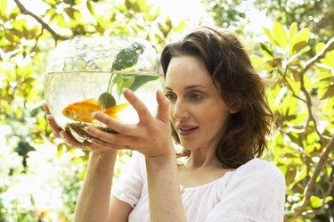 Woman holding fish bowl, smiling