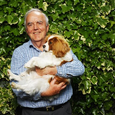 portrait of a man holding a cavalier king charles spaniel