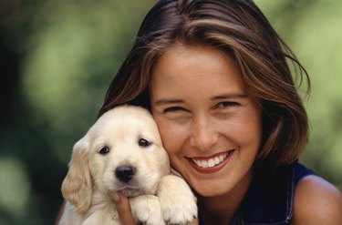 Young woman holding puppy, portrait