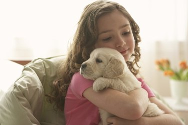 Young girl (8-10) holding dog