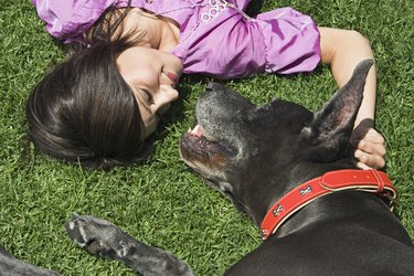 Woman and Great Dane lying on grass