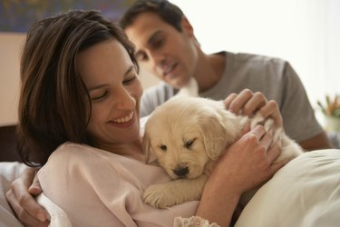 Couple relaxing with dog, smiling