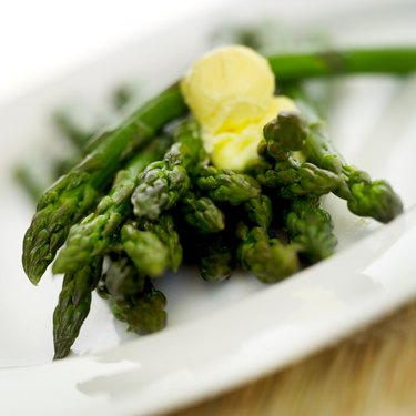 close-up of green beans with a blob of butter on a plate