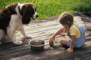 Side profile of a girl feeding her dog